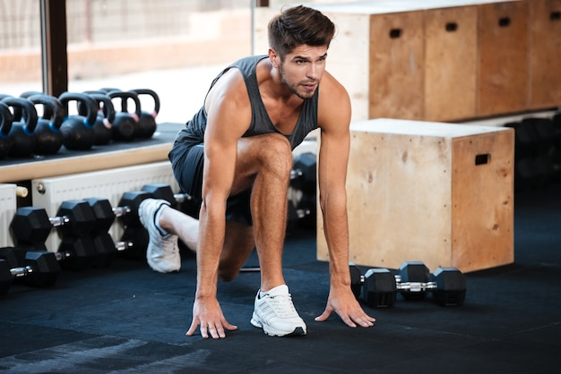 Fitness man doing stretching on the floor in gym