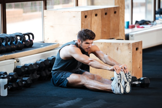 Fitness man doing stretching in gym
