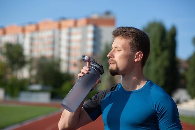 경기장에서 운동하는 동안 휘트니스 남자 식수. 건강한 라이프 스타일 개념입니다. 텍스트를 위한 공간