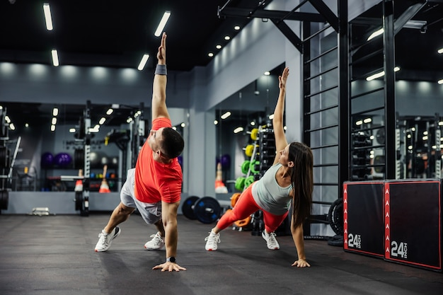 The fitness man and energetic woman are in a plank position with their arms raised and doing full-body in a modern gym. body stability, motivation, better together