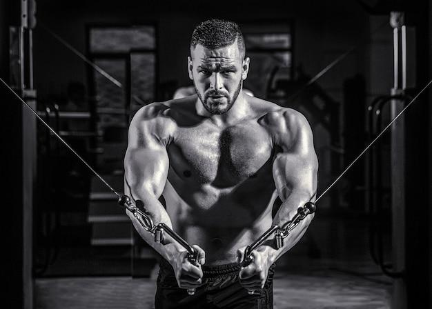フィットネスマンはジムでエクササイズマシンケーブルクロスオーバーでエクササイズを実行します。ジムで大きな筋肉を持つハンサムな男。ジムのマシン。黒と白。