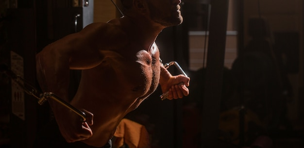 フィットネスマンはジムでエクササイズマシンケーブルクロスオーバーでエクササイズを実行します。ジムで大きな筋肉を持つ男。胸、ケーブルクロスオーバーのエクササイズを行うジムでの筋肉の男のトレーニング。強い男性の胴体腹筋