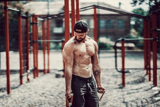 Фитнес человек, работающий с растяжкой в открытом тренажерном зале