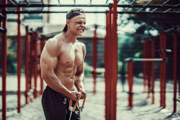 Fitness man exercising with stretching band in outdoor gym.