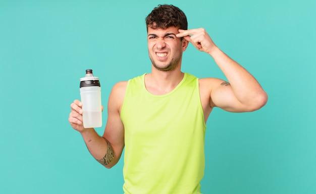 Фитнес-мужчина смущен и озадачен, показывая, что вы сошли с ума, сошли с ума или сошли с ума