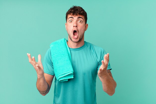 Фитнес-мужчина чувствует себя чрезвычайно шокированным и удивленным, встревоженным и паническим, с напряженным и испуганным взглядом