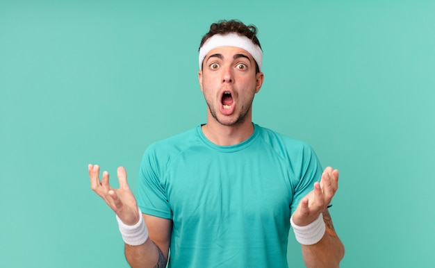 Fitness man feeling extremely shocked and surprised, anxious and panicking, with a stressed and horrified look