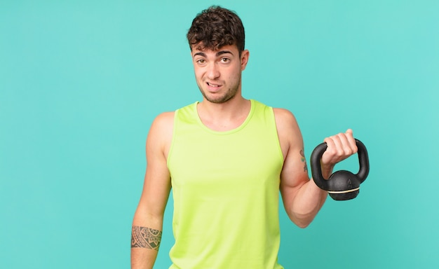 Fitness man feeling puzzled and confused, with a dumb, stunned expression looking at something unexpected