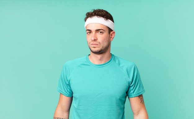 Fitness man feeling sad, upset or angry and looking to the side with a negative attitude, frowning in disagreement