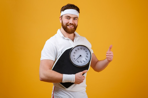 Fitness man holding weight scales and showing thumbs up