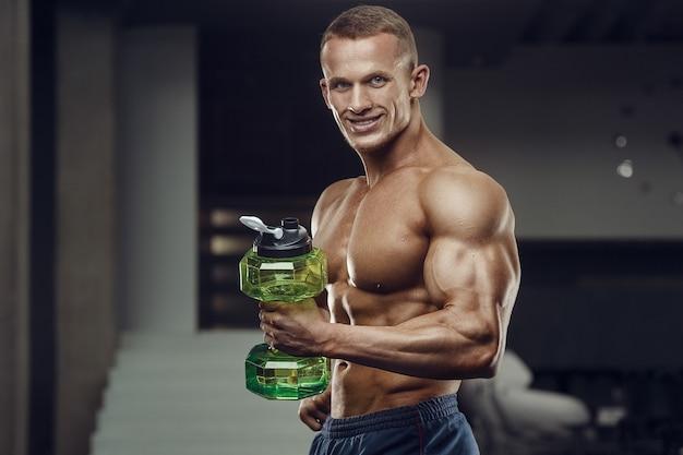 トレーニング後のジムの飲料水でフィットネス男。フィットネスとボディービルの健康的な背景。ジムでエクササイズをしている白人男性。ウォーターボトルとサプリメントの栄養概念