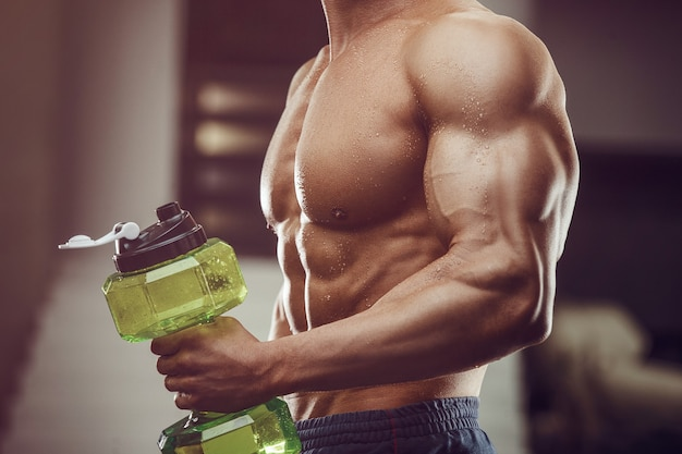 Человек фитнеса в питьевой воде спортзала после тренировки. фитнес и бодибилдинг здоровый фон.