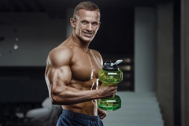 Фитнес человек в тренажерном зале с питьевой водой после тренировки