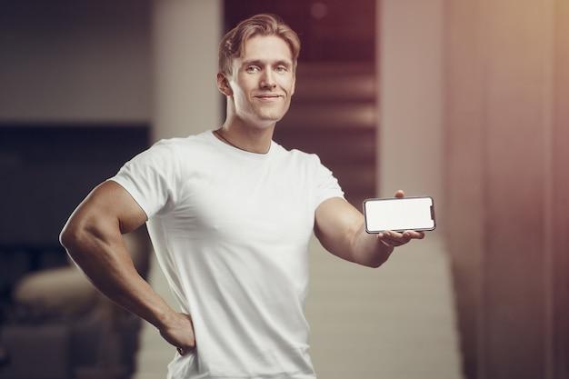携帯電話でジムのフィットネス男。トレーニングフィットネスとボディービルの概念
