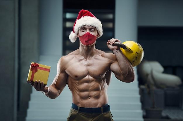 Человек фитнеса в костюме шляпы санта-клауса в тренажерном зале с подарочной коробкой.