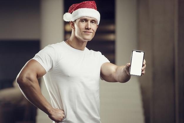휴대 전화 체육관에서 산타 클로스 모자 의상에서 피트 니스 남자. 기쁜 성 탄과 새 해 개념