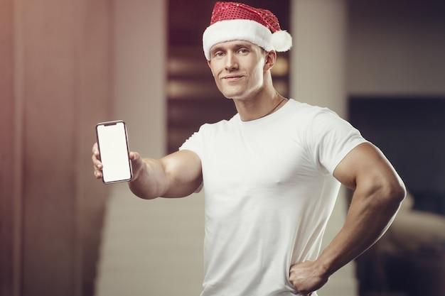 携帯電話とジムでサンタクロースの帽子の衣装のフィットネス男