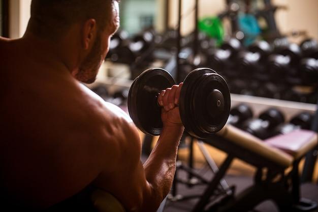 Человек фитнеса поднимаясь гантели. человек подъема гантелей в тренажерном зале, делая упражнения для мышц.