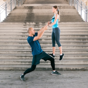 Fitness man lifting the young woman on his leg while practicing exercise near the staircase