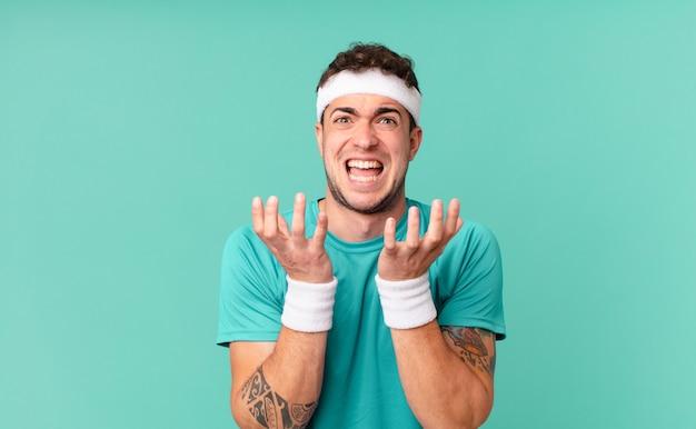 Фитнес-мужчина выглядит отчаянным и разочарованным, подчеркнутым, несчастным и раздраженным, кричит и кричит