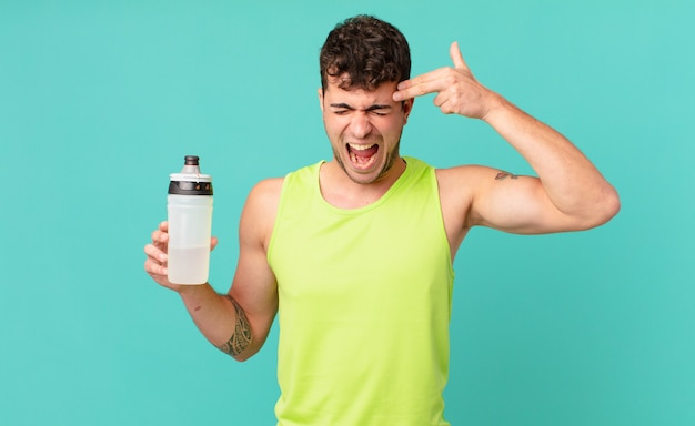 Fitness man looking unhappy and stressed, suicide gesture making gun sign with hand, pointing to head