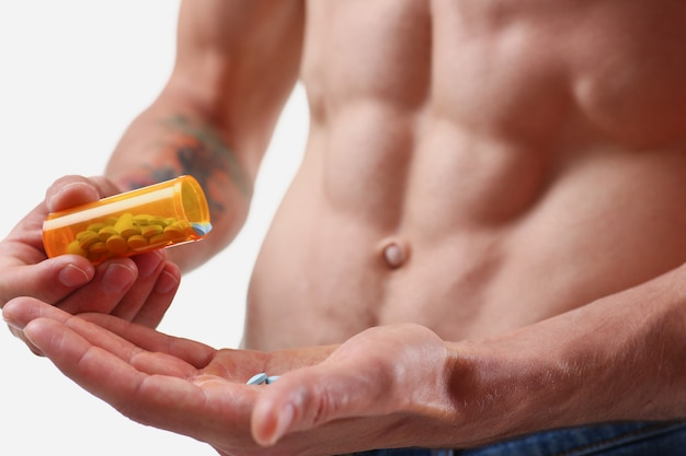Fitness man pours pills from the jar into