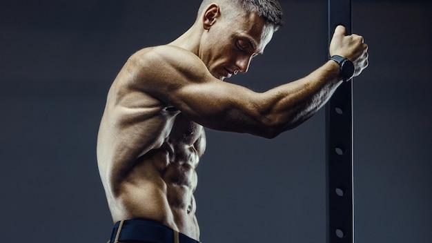 ジムで腹筋をポンピングするフィットネスマン。トレーニングフィットネスとボディービルの健康的な概念の背景。