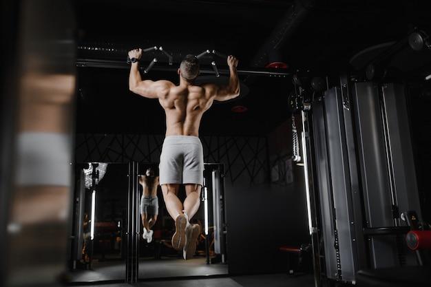 ジムの裸の胴体で懸垂運動をしている筋肉をポンプでくむフィットネス男。背中の筋肉のトレーニングフィットネスとボディービルの概念の背景をポンプアップするハンサムな強い運動選手