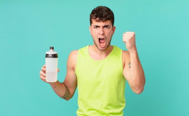 Фитнес-мужчина агрессивно кричит с гневным выражением лица или со сжатыми кулаками, празднуя успех