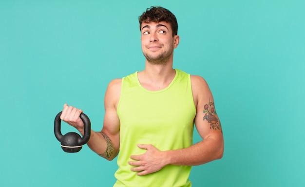 Фитнес-мужчина пожимает плечами, чувствуя замешательство и неуверенность, сомневаясь, скрестив руки и озадаченный взгляд