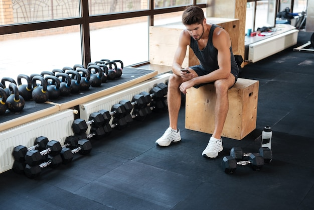 Fitness man sits on the box in gym