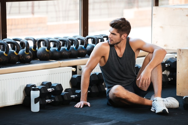 Fitness man sits on the floor and looking away