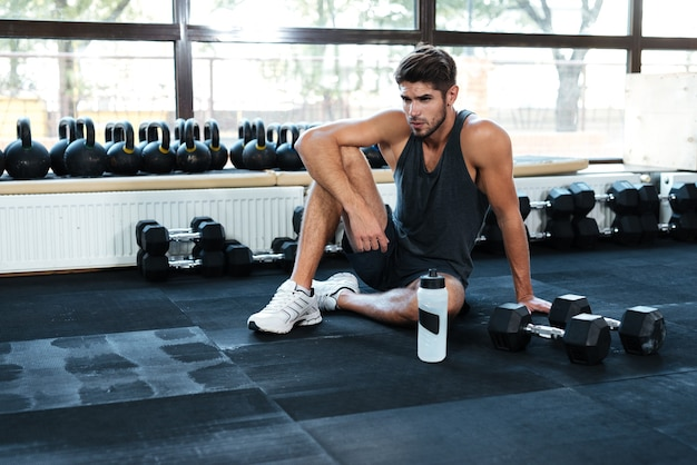 Fitness man sitting down in gym. with weight and bottle