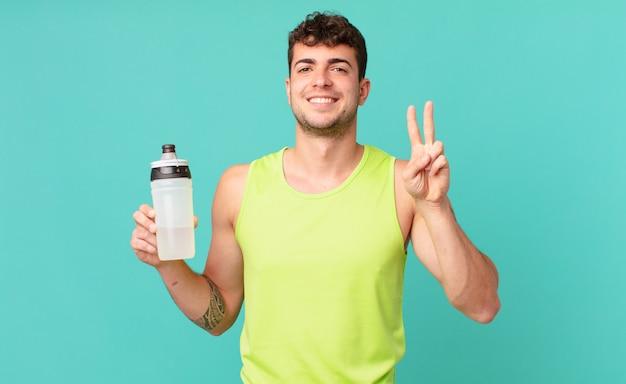 Фитнес-мужчина улыбается и выглядит дружелюбно, показывает номер два или секунду рукой вперед, отсчитывая