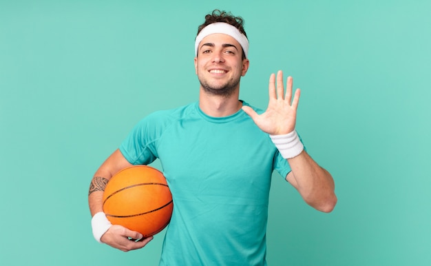 Fitness man smiling and looking friendly, showing number five or fifth with hand forward, counting down