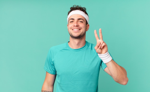 Fitness man smiling and looking friendly, showing number two or second with hand forward, counting down