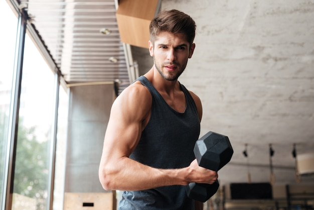 Fitness man stands sideways in gym. looking at the front. with dumbbell