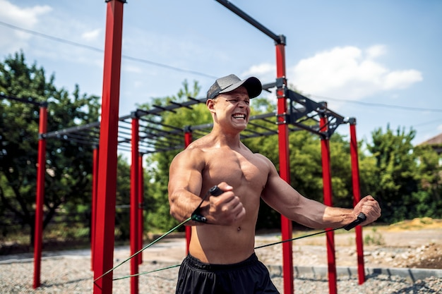 Fitness man training chest with resistance bands at street gym yard. outdoor workout. body workout with equipment outside. elastic rubber band accessory.