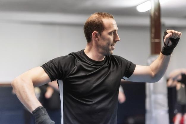 Fitness man warming up in gym. preparing kick boxing combat.