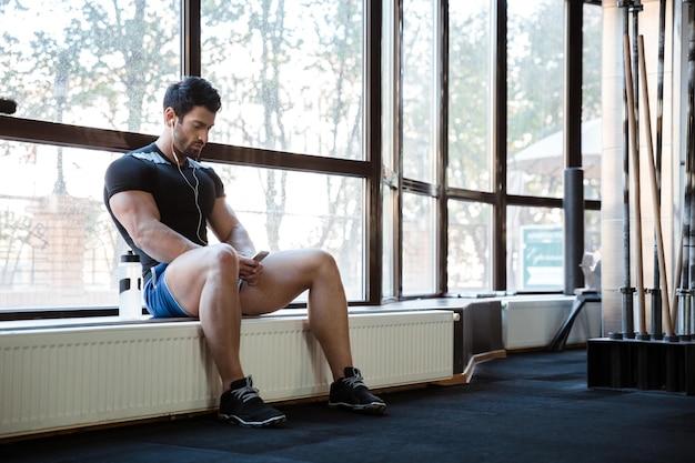 Fitness man wearing blue shorts and black t-shirt listening to music sitting on windowcill