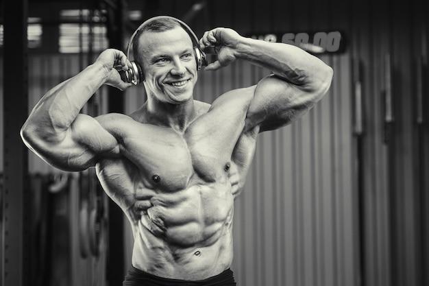 Человек фитнеса с наушниками на тренировке в спортзале. концепция бодибилдинга