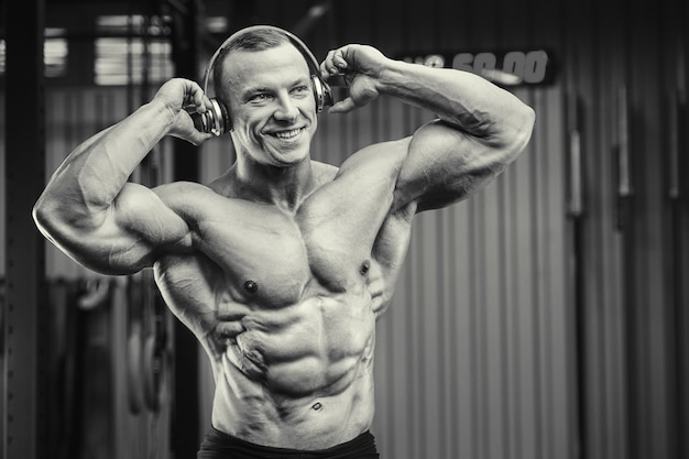 Fitness man with headphones at workout in gym. bodybuilding concept