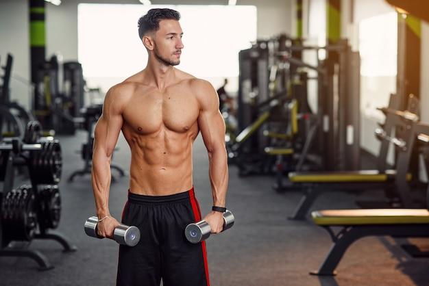 벌 거 벗은 상체 체육관에서 훈련 손과 어깨 동안 아령 운동 피트 니스 남자. 스포티하고 건강한 개념.
