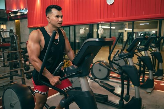 ジムでトレーニングマシンを持つフィットネス男