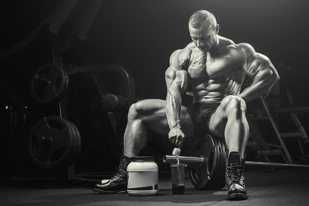 Fitness man at workout in gym with protein powder jar. bodybuilding concept