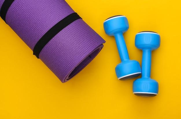 노란색 배경에 피트니스 매트와 아령. 건강한 라이프 스타일, 피트니스 훈련. 평면도