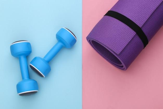 분홍색 파란색 파스텔 배경에 피트니스 매트와 아령. 건강한 라이프 스타일, 피트니스 훈련. 평면도