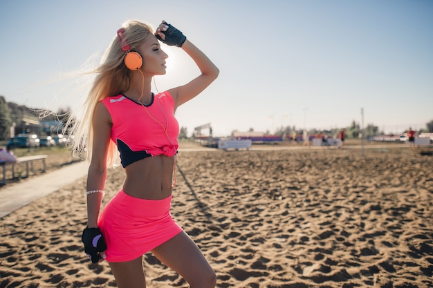 Fitness model athlete girl in colorful sportswear with headphones posing and listening music outdoors on beach or sports ground before workout at evening summer