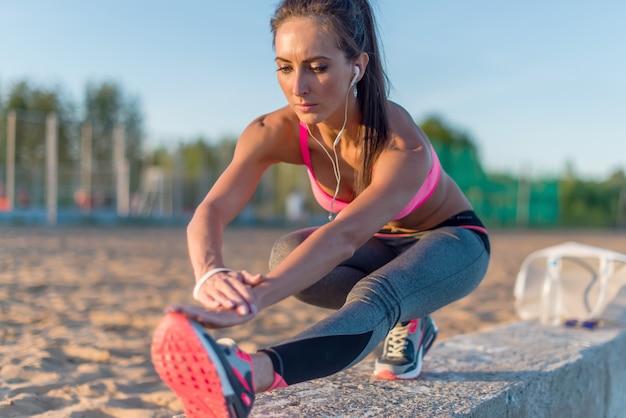 フィットネスモデルのアスリート少女は、彼女のハムストリングス、脚、背中を伸ばしてウォームアップします。夏の夜にビーチやスポーツグラウンドで屋外で音楽を聞くヘッドフォンで運動する若い女性