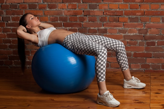 Fitness model exercising with fitball